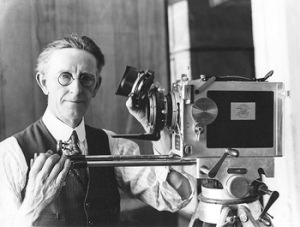 Commonwealth cinematographer Bert Ive in his studio holding a lens component next to a Debrie camera.