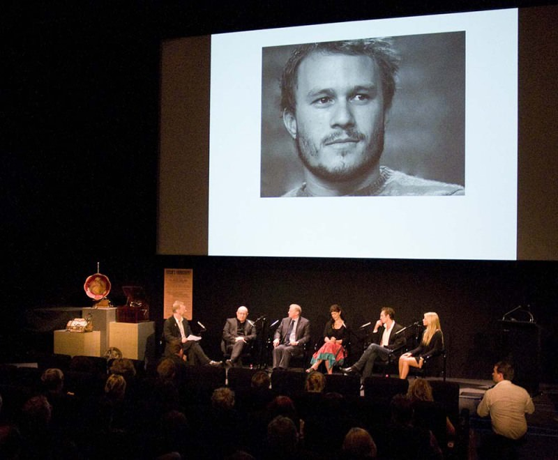 Audience sitting beneath cinema screen showing a close-up of Heath Ledger